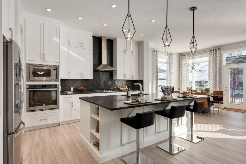 Sterling Homes kitchen photo with large island, stainless steel appliances and white cabinets